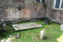 Old grave slabs beside church walls.