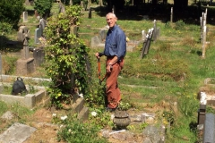 Volunteer Bob clearing ivy off headstones ready to read and record.